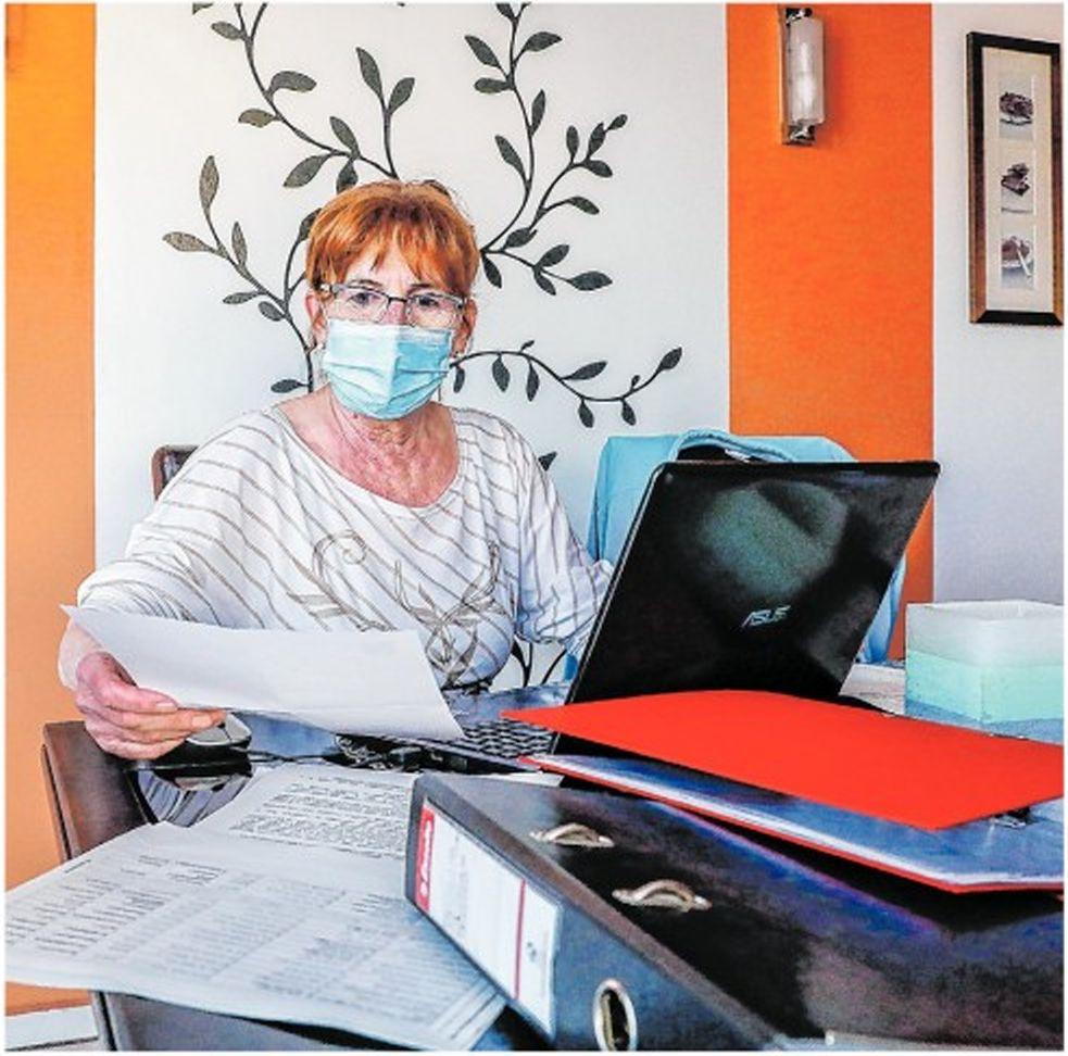 Oláh jánosné, a mozgássérültek vas megyei egyesületének elnöke maszkban az asztal mögött ülve dolgozik